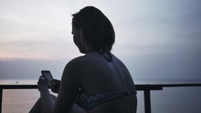 Mädchen auf dem Ufer, das bei einem Smartphone liegt stock video footage