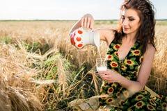 Mädchen auf dem Weizengebiet Mädchen gießt Milch in ein Glas Stockfotografie