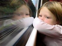 Mädchen auf dem Zug, der aus Fenster heraus schaut lizenzfreie stockbilder