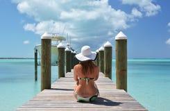 Mädchen auf der Anlegestelle, die zum Ozean schaut. Exuma, Bahamas Lizenzfreie Stockbilder