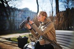 Mädchen auf der Bank, die eine Taube streicht Stockfotos