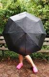 Mädchen auf der Bank, die hinter Regenschirm sich versteckt stockbild