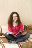 Mädchen auf der Couchlesezeitschrift Lizenzfreie Stockfotos