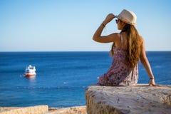 Mädchen auf der Küste, die zum Boot Meer betrachtet Lizenzfreie Stockfotos