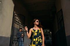 Mädchen auf einem dunklen Hintergrund in der Sonnenbrille, von hinten einen Kerl nahe einer Eisentür, Gitter Streit, lizenzfreie stockfotos