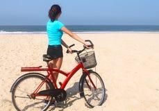 Mädchen auf einem Fahrrad auf dem Strand Stockfotos