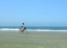 Mädchen auf einem Fahrrad auf dem Strand Lizenzfreie Stockfotografie