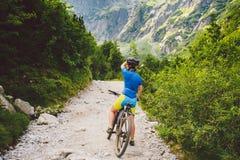 Mädchen auf einem Fahrrad reist nach Slowakei schwarzer Sturzhelm, blaues Hemd, Berge, hohes Tatras, stockbilder