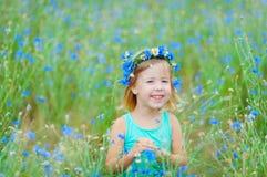 Mädchen auf einem Gebiet, das einen Blumenstrauß von blauen Blumen hält Lizenzfreie Stockfotos