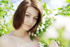 Mädchen auf einem Hintergrund der blühenden Bäume stockbild