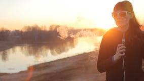 Mädchen auf einem Hintergrund des Flusses raucht eine elektronische Zigarette stock video footage