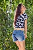Mädchen auf einem Hintergrund des Grüns verlässt kurz gesagt mit Wäscheklammern Stockfotos