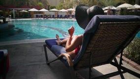 Mädchen auf einem Ruhesessel durch das Pool stock video footage