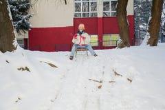 Mädchen auf einem Schlitten, der im Schnee spielt Lizenzfreies Stockbild