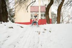 Mädchen auf einem Schlitten, der im Schnee spielt Stockfotos
