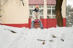Mädchen auf einem Schlitten, der im Schnee spielt Lizenzfreie Stockbilder