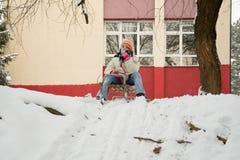 Mädchen auf einem Schlitten, der im Schnee spielt Lizenzfreies Stockfoto
