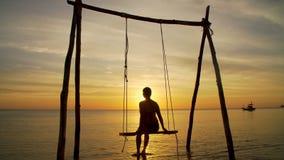 Mädchen auf einem Schwingen durch die Küste auf Sonnenuntergang stock footage