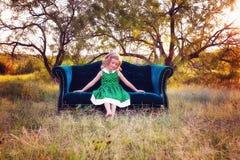 Mädchen auf einem Sofa in der Landschaft Lizenzfreie Stockfotos