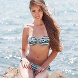 Mädchen auf einem Stein Strandmeer oder -ozean stockfoto