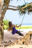 Mädchen auf einem Strand Fahrten auf ein Schwingen stockfotos
