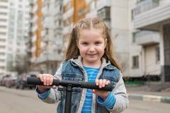 Mädchen auf einem Trittroller lizenzfreies stockbild