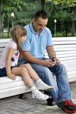 Mädchen auf einem Weg im Park mit ihrem Vater Lizenzfreie Stockfotografie