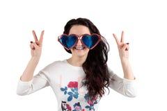 Mädchen auf einem weißen Hintergrund mit großen Gläsern und ihren Händen oben stockbild