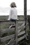 Mädchen auf einem Zaun lizenzfreies stockbild