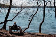 Mädchen auf einer Bank durch den See Stockbild