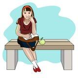 Mädchen auf einer Bank mit einem Notizbuch und einem Apfel Stockbild