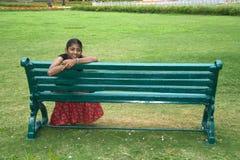 Mädchen auf einer Garten-Bank Stockbilder