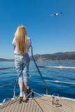 Mädchen auf einer Yacht, die das blaue Meer betrachtet Lizenzfreies Stockbild