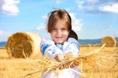 Mädchen auf Erntefeld mit Strohballen Stockfotografie