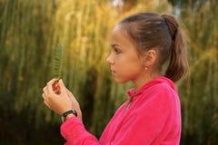 Mädchen auf Grün lässt Hintergrund Stockfotografie