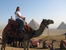 Mädchen auf Kamel durch große Pyramiden Stockfotografie