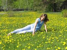 Mädchen auf Löwenzahnrasen lizenzfreies stockfoto
