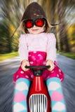 Mädchen auf laufendem Auto des Spielzeugs Stockbild
