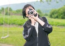 Mädchen auf Natur mit einer Kamera Lizenzfreies Stockbild