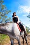 Mädchen auf Pferdehintergrund des Blaus Lizenzfreie Stockbilder