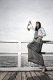 Mädchen auf Pier mit Kerosinlampe Stockfoto