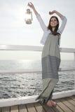 Mädchen auf Pier mit Kerosinlampe Lizenzfreies Stockbild