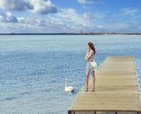 Mädchen auf Pier mit Schwan Stockfoto