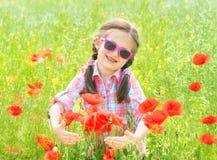 Mädchen auf rotem Blumenmohnblumenfeld Stockbild