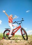 Mädchen auf rotem Fahrrad Lizenzfreies Stockfoto
