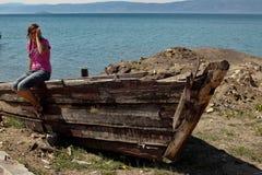 Mädchen auf ruiniertem Boot Stockfotografie