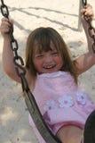 Mädchen auf Schwingen mit Lächeln Stockfotos