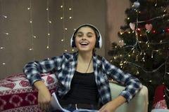 Mädchen auf Sofa mit Kopfhörer nahe Weihnachtsbaum lizenzfreies stockbild