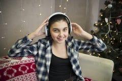 Mädchen auf Sofa mit Kopfhörer nahe Weihnachtsbaum Stockfotos