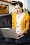 Mädchen auf Sofa mit Laptop, zeigt sie das displa an Stockfotos